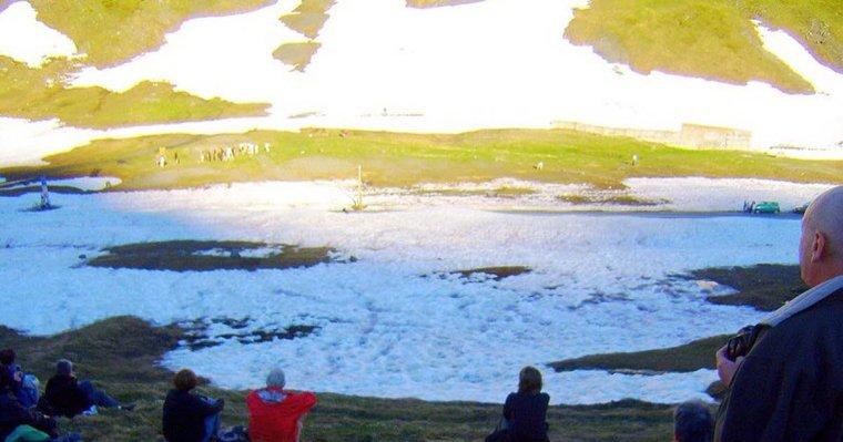 La gente, seduta attorno al cromlech, assiste all'abbraccio delle due falci di ombra aspettando l'ultimo raggio di sole allineato sulla pietra appuntita.